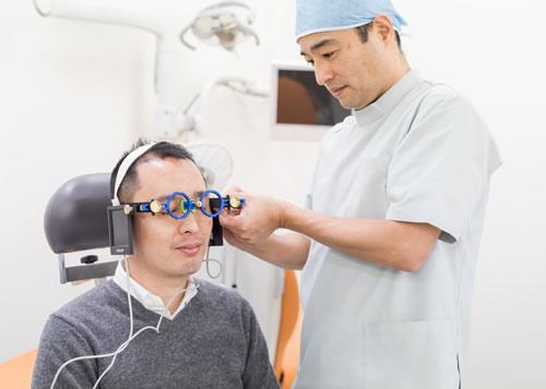 矯正治療のために顎運動の検査をしている歯科医師