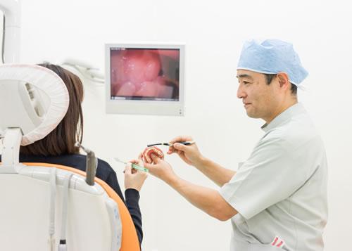 松原市の歯医者すが歯科の歯科医師が歯周病の患者にブラッシングを教えている