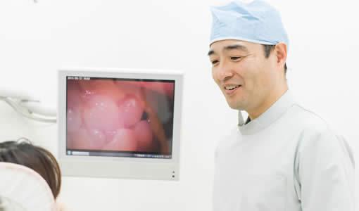 松原市の歯医者すが歯科の歯科医師菅人志が患者に説明している